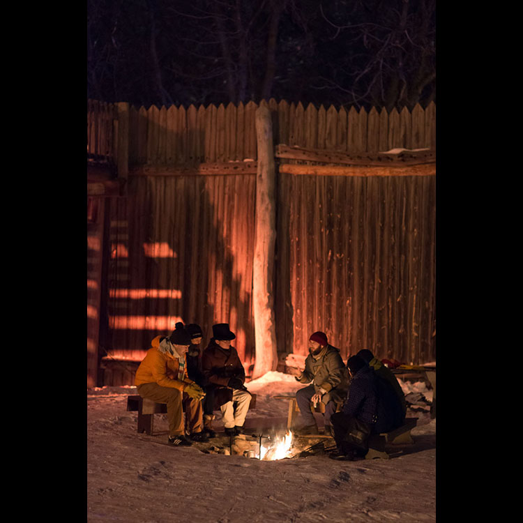 Voyageurs gather around the fire to tell stories.