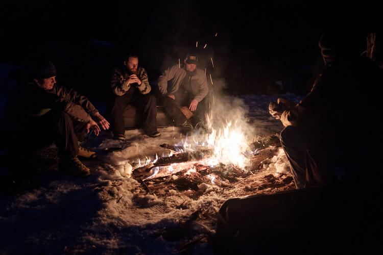 Huddled around the campfire after dark