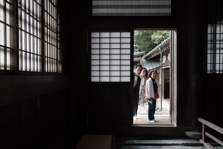 Tourists gaze into Buddist temple door