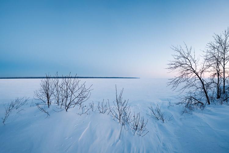 Snow drifts cover Lake Winnipeg at dusk