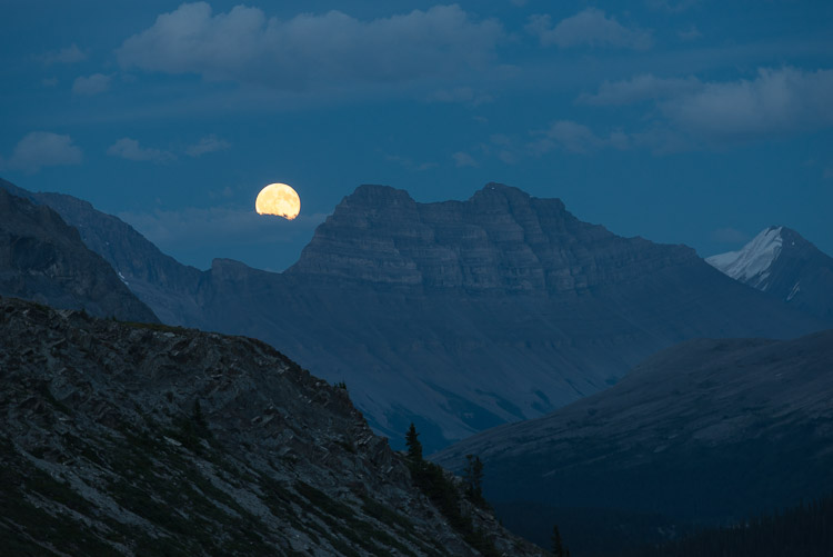 Moonrise over mountains on a warm summer evening