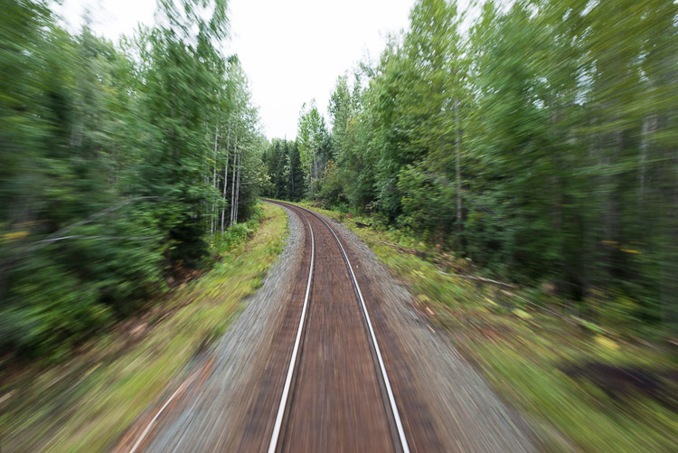 Fast moving train on railroad tracks - blurry trees
