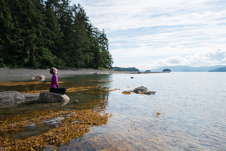 Joyful girl laughing on a rock at the Haida Gwaii coast