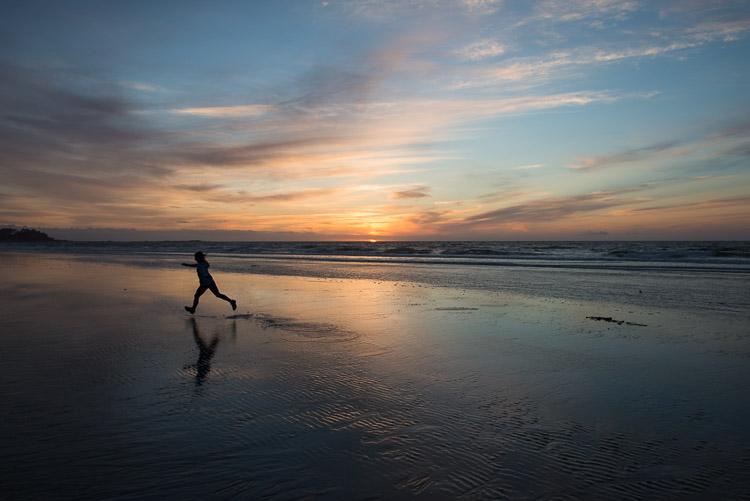 Silhouette of playful girl at sunset on Agate Beach - Haida Gwaii - Naikoon