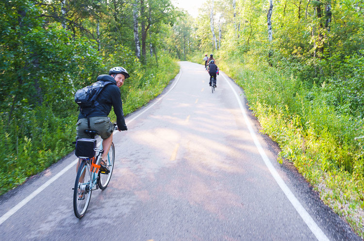 Happy cyclist looking back as he rides through forest