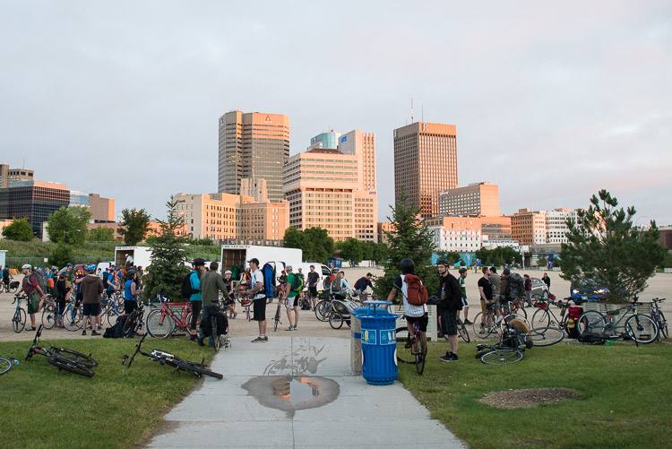 Winnipeg skyline at sunrise as cyclists gather to ride out to the Winnipeg Folk Festival site