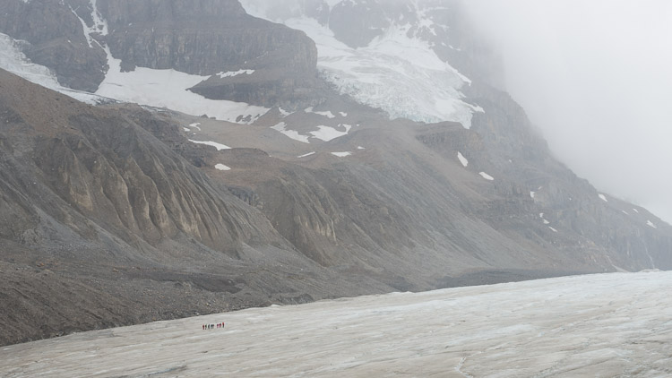 Distant hikers carefully cross the Athabasca glacier