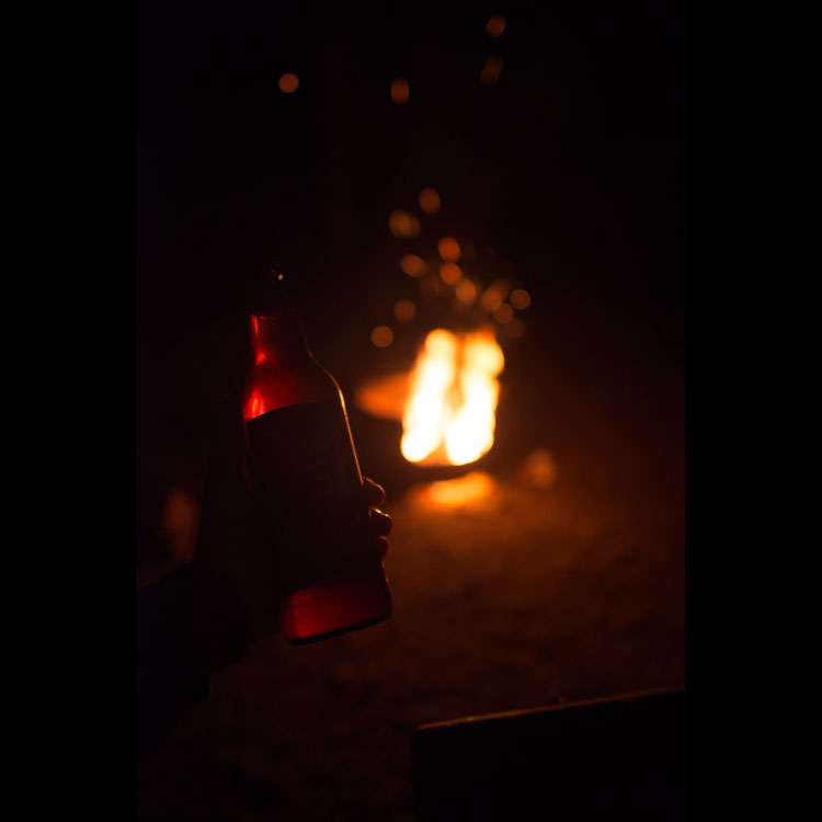 Drinking beer at campfire