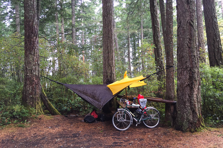 Hammock and poncho shelter from storm at camp