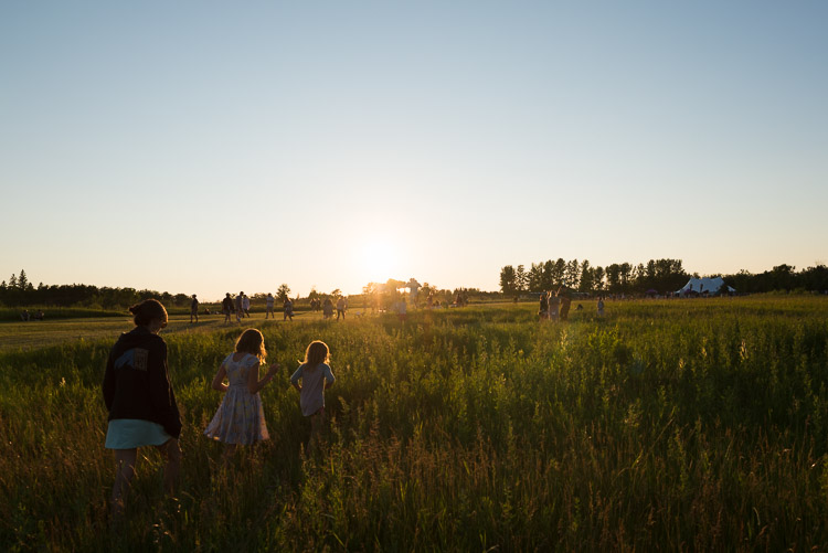 Family wandering through the Winnipeg Folk Festival fields at sunset
