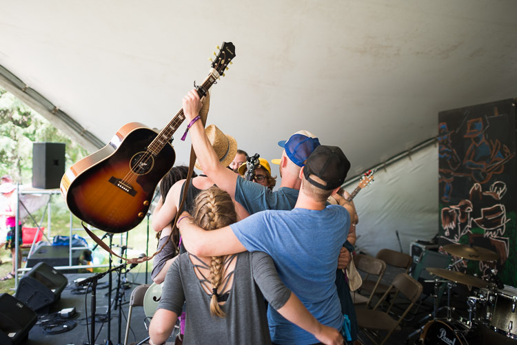 The Crooked Brothers engage in a group hug on stage with their musical apprentices